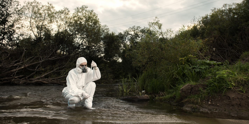 Scientist working alone in the field testing water in a stream