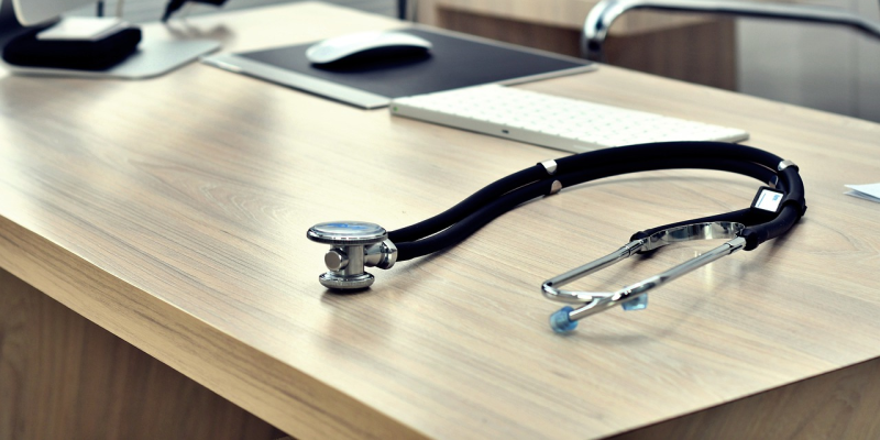 Image of a desk with computer and stethoscope